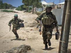 African Union peacekeeping forces run to take up positions during clashes with Islamist militants in Mogadishu.