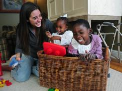 Katie Davis plays with her daughters Patricia, 3, and Grace, 5, Wednesday in her parents' home. Davis is raising more than a dozen AIDS orphans in Uganda.