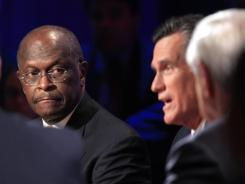 Herman Cain listens while Mitt Romney speaks during Tuesday's GOP  presidential debate.