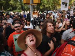 """Occupy Wall Street"" protesters yell up to the residence of News Corp. CEO Rupert Murdoch on Tuesday in New York City."