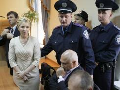 Police officers lead former Ukrainian Prime Minister Yulia Tymoshenko out of the courtroom after she was sentenced to seven years in prison.