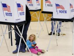 A Colorado voter casts a ballot while her daughter watches last fall.