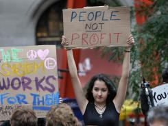 A young woman holds up a sign as passersby take in the scene at the Occupy Wall Street headquarters at Zuccotti Park in New York on Tuesday.