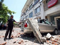 An Indonesian man looks at a minivan crushed by a chunk of concrete that fell from a building after an earthquake in Kuta, Bali, Indonesia on Thursday.