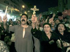 Egyptian Copts hold Christian crosses and chant slogans as they demonstrated on Oct. 4 against sectarian violence in downtown Cairo.  In the past few weeks, riots have broken out at two churches in southern Egypt, prompted by Muslim crowds angered by rumors that Christians were building new churches.