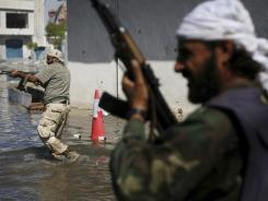 Revolutionary fighters run to take cover on the streets of Sirte, Libya, on Wednesday.