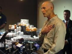 Florida Gov. Rick Scott talks about prescription-drug abuse with a million dollars' worth of pain pills in the background. The pills were turned in by pain clinics to meet the deadline for a law made to control pill mills.