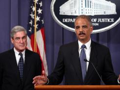 Announcing allegations: Attorney General Eric Holder, right, and FBI director Robert Mueller.