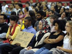People listen to others voice their concerns about the Alabama HB56 law at a town hall meeting at Glen Iris Elementary School in Birmingham, Ala. The federal appeals court blocked for now a part of the law that requires schools to check the immigration status of students.
