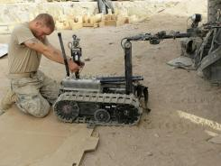 Army Spc. Nathaniel Anselmo repairs a robot in 2010 in Khakrez, Afghanistan.
