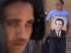 A pro-Mubarak supporter flashes his poster outside the Cairo court last month where the former leader and his two sons are on trial.