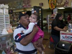 Grocery owner Andres Miguel, 54, kisses his 10-month-old granddaughter, Jacqueline. He fears Alabama's immigration law will hurt his business and force friends to leave town.