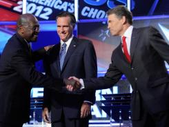 Herman Cain, Mitt Romney and Rick Perry greet one another at the start of the Republican presidential debate. These candidates took the brunt of Tuesday's attacks.