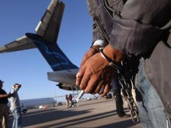 An undocumented Guatemalan immigrant, chained for being charged as a criminal, prepares to board a deportation flight to Guatemala City on June 24 in Mesa, Ariz.