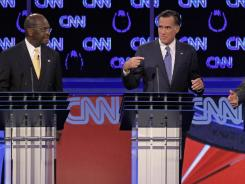 Republican presidential candidates Herman Cain, left, watches as former Massachusetts governor Mitt Romney, center, and Texas Gov. Rick Perry speak during a Republican presidential debate.