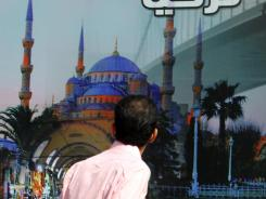 An  Iraqi man looks at a poster advertising travel to Turkey in Baghdad on Tuesday.