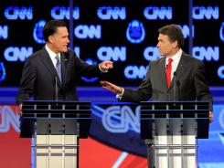 Former Massachusetts governor Mitt Romney, left, and Texas Gov. Rick Perry participate in a Republican presidential debate Tuesday on CNN.