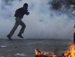 Protesters throw stones in Syntagma Square, Athens, during violent demonstrations on Thursday.