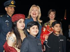 Pakistani children welcome Secretary of State Hillary Clinton upon her arrival in Islamabad on Thursday.
