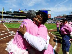 Breast cancer survivors Lesley Hudson, right, and Kathy Bernhartt, both of Atlanta, hug during a breast cancer awareness presentation prior to a recent baseball game in Atlanta.