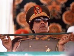 Col. Moammar Gadhafi  holds a baton during a  review of  troops at  the 18th anniversary celebration of Libya's revolution in Tripoli in 1987.