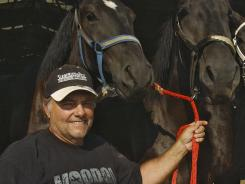 Terry Thompson stands with some of his award-winning Percheron horses on his farm near Zanesville, Ohio. Thompson freed dozens of exotic animals he owned, then killed himself Tuesday, officials say.