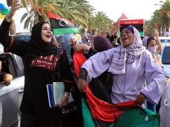 Celebrating in the streets:  Libyans wave their new national flag Thursday as they celebrate in Tripoli following news of Moammar Gadhafi's death.