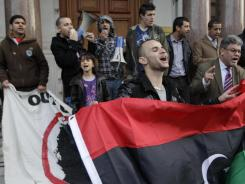 Libyans react to the death of Moammar Gadhafi outside the Libyan Embassy in London.
