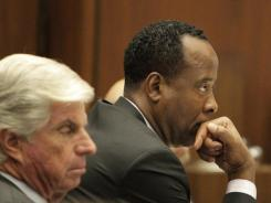 Dr. Conrad Murray, joined by his defense attorney J. Michael Flanagan, left, looks on during his involuntary manslaughter trial in Los Angeles on  Friday.
