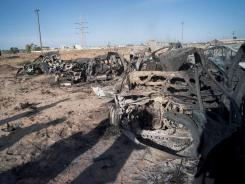 The wreckage of burnt vehicles from a convoy of pro-Gadhafi fighters trying to flee the town of Sirte lies on the edge of town Thursday.
