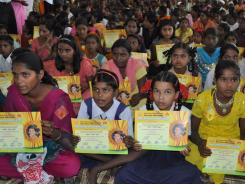 Indian girls hold up their name change certificates during a ceremony in Satara.
