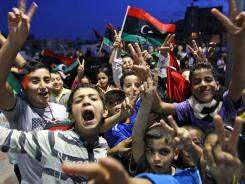 Children celebrate on Friday in Tripoli, Libya. Libyans marked the death of dictator Moammar Gadhafi.