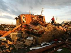 An emergency worker combs through the wreckage of a destroyed home after a tornado hit April 27 in Smithville, Miss.