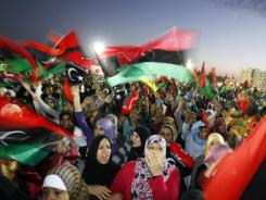 People celebrate in Benghazi, Libya, as the transitional government declares the country's official liberation Sunday.