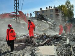 Turkish rescue workers scramble through the rubble in a search for survivors on Monday.