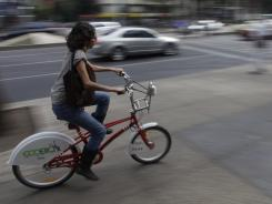 A woman rides an Ecobici bicycle in Mexico City. The bike-sharing program has attracted more than 30,000 people, and it has a six-week waiting period for new members.