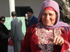 An unidentified Tunisian woman shows ink on her finger after voting in the al-Aouina suburb north of Tunis.