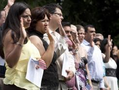 Ruth Salamanca, left, of El Salvador, takes the oath of citizenship along with others during a naturalization ceremony at George Washington's Mount Vernon Estate in Virginia on July 4. Immigrants traditionally take two paths to reaching this country: Family ties or employment opportunities.