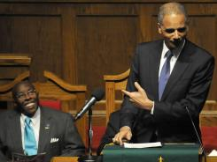 Rev. Calvin Woods, left, laughs as U.S. Attorney General Eric Holder speaks during a remembrance service for the late Rev. Fred Shuttlesworth at 16th Street Baptist Church in Birmingham on Sunday.