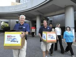 Greg York, left, President of Vann York Auto Group, and Bobby Smith, President of United Way of Greater High Point, carry boxes of food collected by the staff of High Point Regional Health System on Sept. 13 in High Point, N.C.