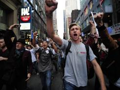 Occupy Wall Street participants chant slogans on their way to stage a demonstration on Times Square in New York on Oct. 15.