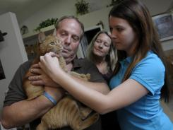 Mike Cage, daughter Ashley, right, and wife Dawn play with Bynx, a cat that belonged to Heather, at their home in Minneola, Fla. Mike Cage says he got the news of the death of his daughter Heather the wrong way.