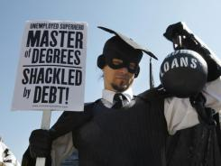 "Gan Golan of Los Angeles, dressed as the ""Master of Degrees,"" holds a ball and chain representing his college loan debt during an  ""Occupy D.C."" protest  Oct. 6."