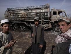 Afghan youths stand near a fuel truck that exploded in Parwan province on Wednesday.