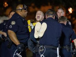 A protester with the Occupy Atlanta demonstration is arrested after refusing to leave Woodruff Park early Wednesday after Mayor Kasim Reed revoked his executive order allowing the protesters to camp there.