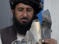 Pakistani tribal elder Karim Khan shows the remains of a missile reportedly fired by a U. S. drone on a village.