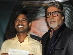 Sushil Kumar, left, with Bollywood actor Amitabh Bachchan, shows $1 million check after winning on an Indian game show.