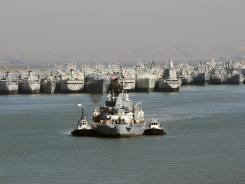 Out of retirement for now: Tugboats tow the USS Iowa, the last battleship from WWII era, away from the naval ghost fleet Thursday to Benicia, Calif.