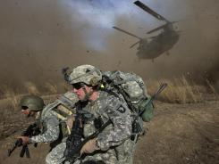 This 2009 file photograph shows US Army soldiers and Afghan National Army soldiers racing to get out of the way of a CH-47 Chinook helicopter landing in hostile territory in Khost province near the Afghan-Pakistan border.