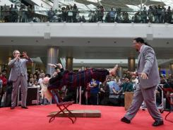 Magicians Penn Jillette, right, and Raymond Teller perform a trick at Westfield Shopping centre in London.
